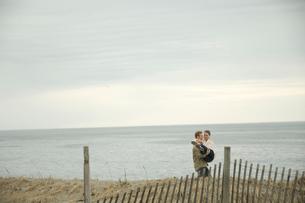 浜辺ではしゃぐカップルの写真素材 [FYI04070590]