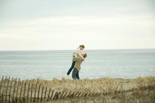 浜辺ではしゃぐカップルの写真素材 [FYI04070592]
