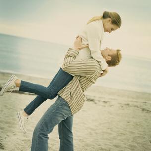 浜辺で抱き合いはしゃぐカップルの写真素材 [FYI04070596]