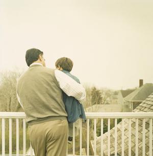 テラスで孫息子を抱きかかえる祖父の写真素材 [FYI04070631]