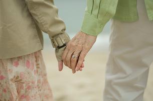 浜辺で手を繋ぐ祖母と孫娘の手元の写真素材 [FYI04070641]