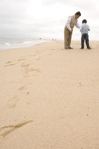 浜辺に立っている祖父と孫息子の写真素材 [FYI04070642]