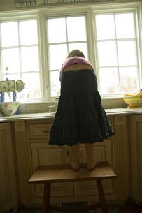 キッチンで台の上にたって手を洗う少女の後姿の写真素材 [FYI04070645]