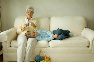 編み物をする祖母の膝に寝る孫娘の写真素材 [FYI04070657]