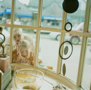 お店の中を覗く祖母と孫娘の写真素材 [FYI04070658]