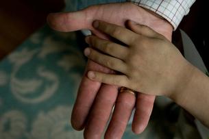 重ね合わせた祖父と孫息子の手のひらの写真素材 [FYI04070659]