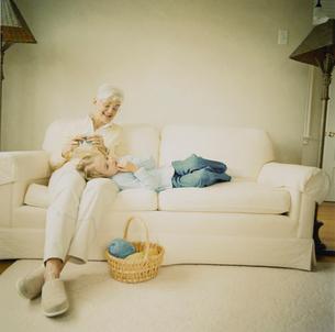 編み物をする祖母の膝に寝る孫娘の写真素材 [FYI04070663]