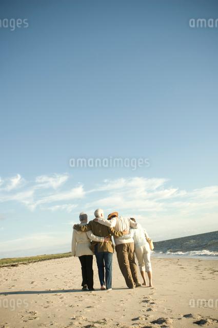 肩を組んで浜辺を歩くシニアカップル2組の写真素材 [FYI04070668]