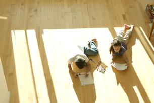 床に寝そべりお絵かきをする少年と少女の写真素材 [FYI04070687]