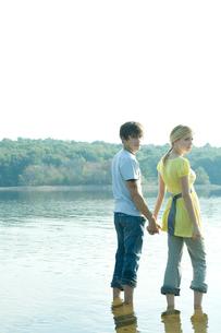 手をつなぎ湖畔にはいる男女の写真素材 [FYI04070752]