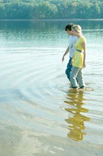 手をつなぎ湖畔にはいる男女の写真素材 [FYI04070754]