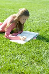 芝生で勉強する女子学生の写真素材 [FYI04070769]