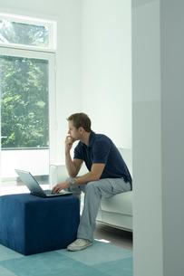 ソファでコンピュータをする男性の写真素材 [FYI04070779]