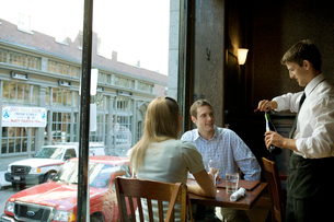 ワインをあけるウエイターとカップルの写真素材 [FYI04070786]