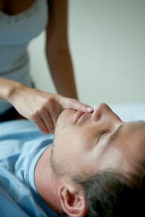 ベッドの上で男性の唇に指をあてる女性の写真素材 [FYI04070825]