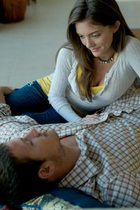 室内で寝転がって見つめ合うカップルの写真素材 [FYI04070865]