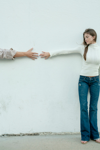 白い壁際で手を繋ごうとするカップルの写真素材 [FYI04070867]