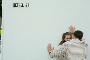 白い壁際でささやくカップルの写真素材 [FYI04070870]