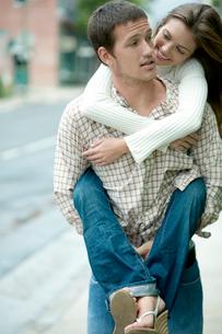 女性を負んぶして歩く男性の写真素材 [FYI04070872]