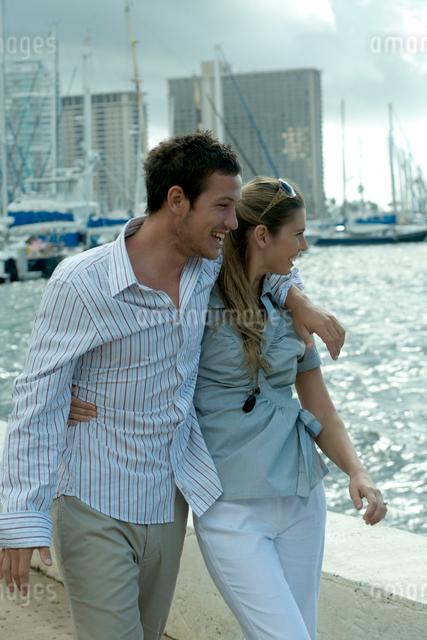 海沿いを肩を組んで歩くカップルの写真素材 [FYI04070874]