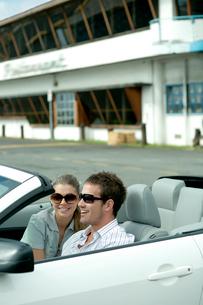 オープンカーを駐車場に止めて寛ぐカップルの写真素材 [FYI04070877]