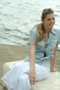 海沿いに座ってリラックスする女性の写真素材 [FYI04070878]