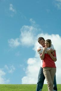 芝生の上で女性を抱きしめる男性の写真素材 [FYI04070890]