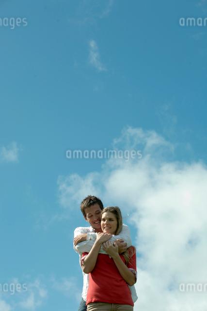 青空の下で女性を抱きしめる男性の写真素材 [FYI04070891]