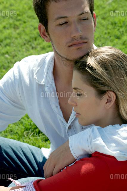 芝生の上に座って女性を抱き寄せる男性の写真素材 [FYI04070893]