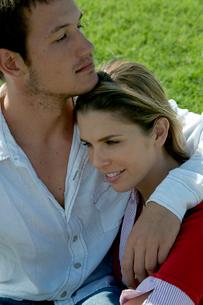 芝生の上に座って女性を抱き寄せる男性の写真素材 [FYI04070895]