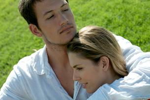 芝生の上に座って女性を抱き寄せる男性の写真素材 [FYI04070896]