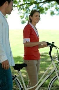 公園で自転車を引く女性と側を歩く男性の写真素材 [FYI04070900]