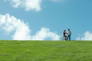 公園で自転車に乗る女性と側を歩く男性の写真素材 [FYI04070901]
