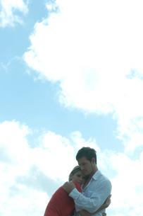 海沿いの岩場で女性を抱きしめる男性の写真素材 [FYI04070903]