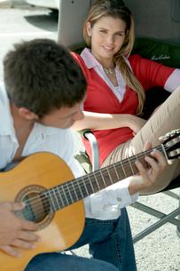 ギターを弾く男性と側で聴き入る女性の写真素材 [FYI04070905]