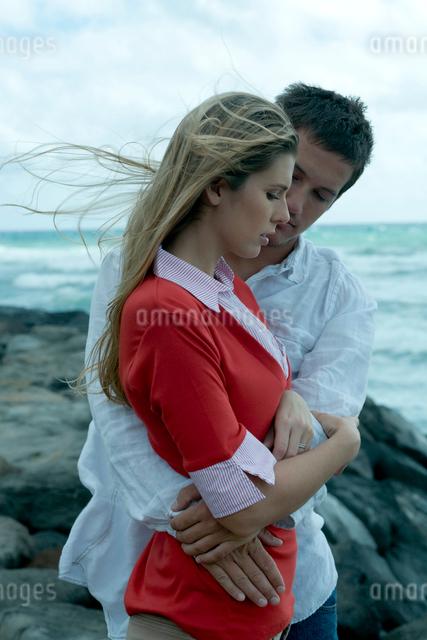 海沿いの岩場で女性を抱きしめる男性の写真素材 [FYI04070906]