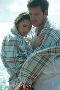 海沿いで毛布を被って抱き合うカップルの写真素材 [FYI04070908]