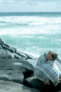 海沿いの岩場で毛布を被って座る女性の写真素材 [FYI04070910]