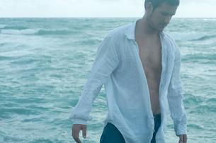 海沿いの岩場に立つ男性の写真素材 [FYI04070911]