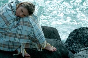 海沿いの岩場で毛布を被って座る女性の写真素材 [FYI04070912]