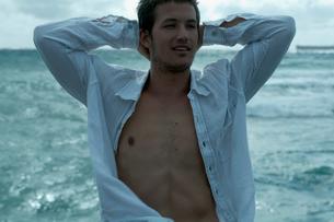 海沿いでリラックスする男性の写真素材 [FYI04070914]