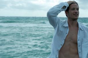 海沿いでリラックスする男性の写真素材 [FYI04070915]