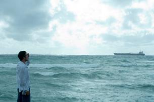 海沿いで遠くの船を眺める男性の写真素材 [FYI04070916]