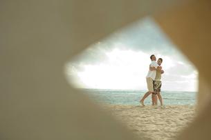 海岸で抱き合うカップルの写真素材 [FYI04070922]
