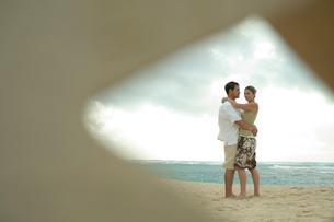 海岸で抱き合うカップルの写真素材 [FYI04070924]