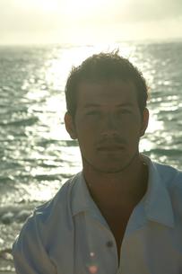 夕暮れの海岸でたそがれる男性の写真素材 [FYI04070928]