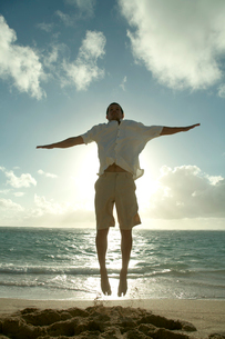 夕暮れの海岸でジャンプをする男性の写真素材 [FYI04070929]