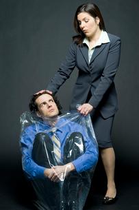 上司にゴミ袋に入れられるビジネスマンの写真素材 [FYI04070934]