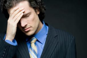 片手で頭を抱えて悩むビジネスマンの写真素材 [FYI04070935]