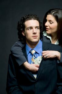 胸ポケットに現金を入れられるビジネスマンの写真素材 [FYI04070939]